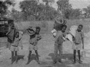 Boys from Booroloola return from  a trip with their missionary. Here they are loaded with their blankets and swags (c1966)