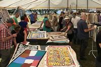 People looking at artworks on a table at the market.