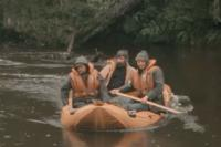 three men on a rubber boat paddling in a river