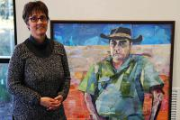 Amanda King next to her portrait of Professor Mick Dodson